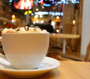 A cup of Wild Coffee's staff favourite (a mocha with peppermint sprinkles), with the cozy seating area in the background. Photos by Ellie Shortt